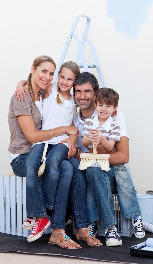 Retrato de una familia feliz que adorna un cuarto imagen de archivo libre de regalías