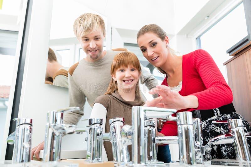 Retrato de una familia feliz que busca un nuevo grifo del fregadero del cuarto de baño fotos de archivo