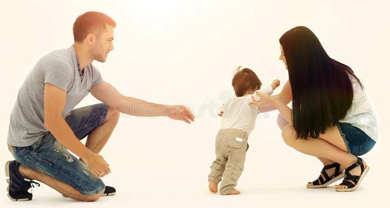 Retrato de una familia feliz que enseña a un niño a caminar foto de archivo