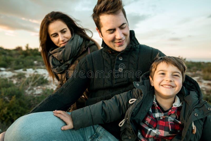 Retrato de una familia que sonríe y feliz en el campo Matrimonio con un niño en el campo imagen de archivo