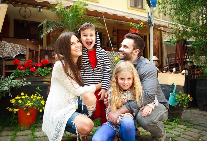 Retrato de una familia sonriente feliz en jardín de flores imagenes de archivo