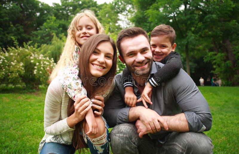 Retrato de una familia sonriente feliz en parque de la ciudad fotografía de archivo libre de regalías