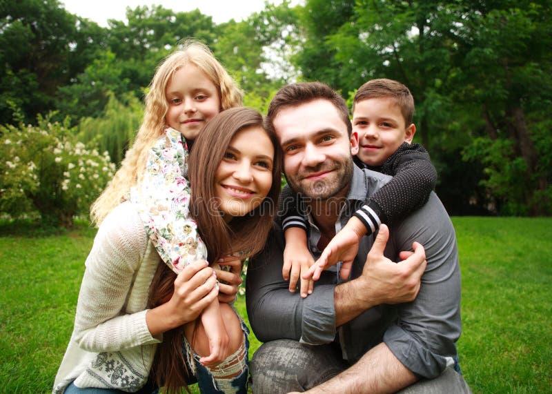 Retrato de una familia sonriente feliz en parque de la ciudad foto de archivo
