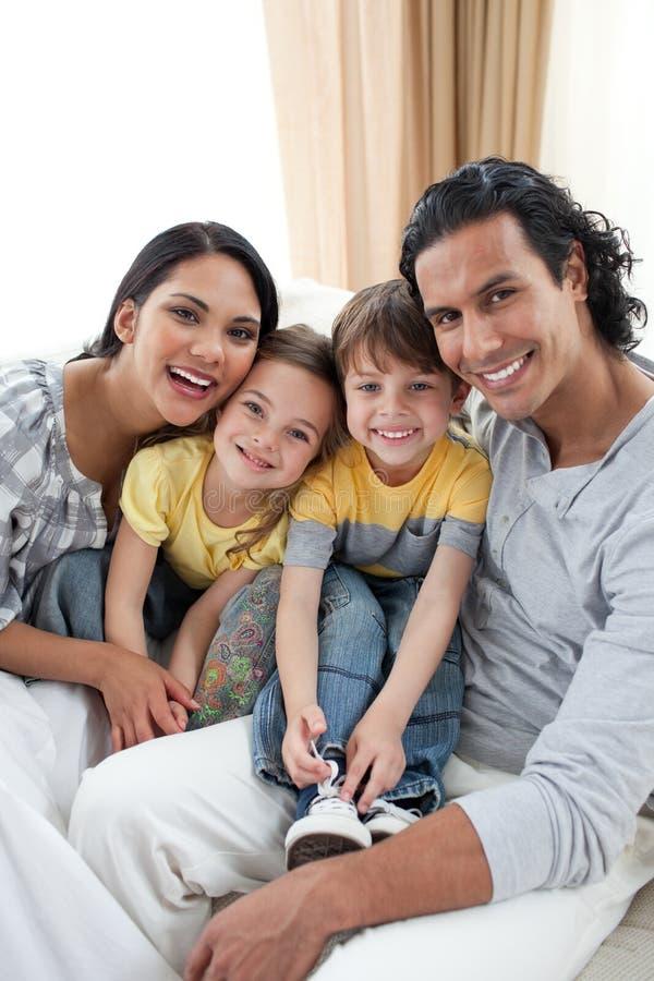 Retrato de una familia sonriente que se sienta en el sofá fotos de archivo libres de regalías