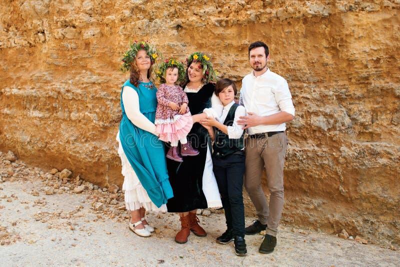 Retrato de una familia de tres generaciones en ropa y guirnaldas retras rústicas del vintage contra un fondo de la pared de la ar fotografía de archivo