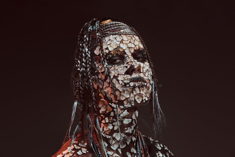 Retrato de una hembra africana asustadiza del chamán con una piel agrietada aterrorizada y dreadlocks Concepto del maquillaje imágenes de archivo libres de regalías