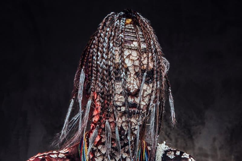Retrato de una hembra africana asustadiza del chamán con una piel agrietada aterrorizada y dreadlocks Concepto del maquillaje fotografía de archivo libre de regalías