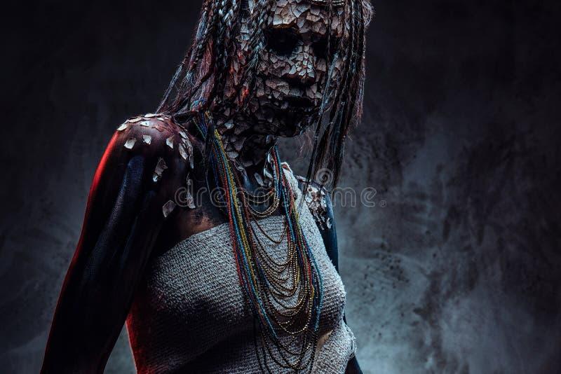 Retrato de una hembra africana asustadiza del chamán con una piel agrietada aterrorizada y dreadlocks Concepto del maquillaje fotos de archivo