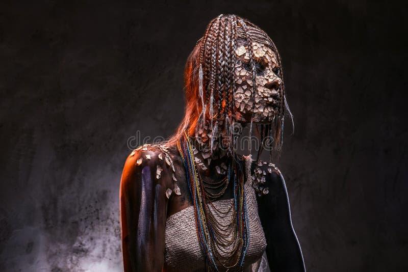 Retrato de una hembra africana asustadiza del chamán con una piel agrietada aterrorizada y dreadlocks Concepto del maquillaje foto de archivo libre de regalías