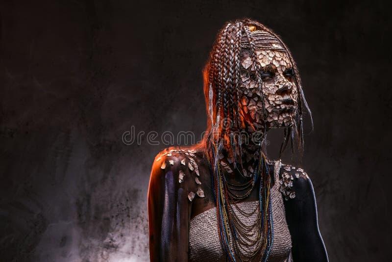 Retrato de una hembra africana asustadiza del chamán con una piel agrietada aterrorizada y dreadlocks Concepto del maquillaje fotos de archivo libres de regalías