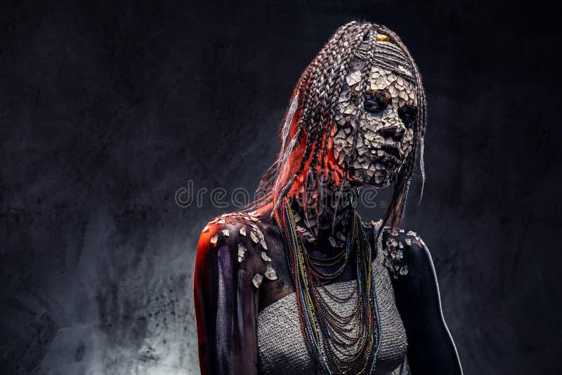 Retrato de una hembra africana asustadiza del chamán con una piel agrietada aterrorizada y dreadlocks Concepto del maquillaje foto de archivo