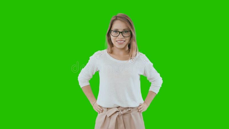 Retrato de una hembra rubia joven con una expresión seria alegre con los vidrios, vestido en un traje del estilo de la oficina fotos de archivo libres de regalías