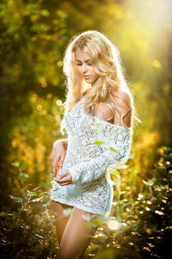 Retrato de una hembra rubia joven sensual en campo en vestido atractivo del cortocircuito del blanco fotos de archivo