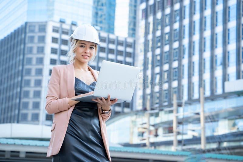 Retrato de una hermosa mujer empresaria desarrolladora de ingeniería sostiene portátil trabajar Confidente al aire libre imagenes de archivo