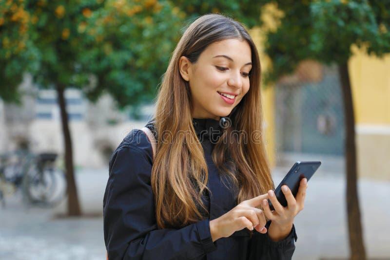 Retrato de una hermosa mujer sonriente usando un teléfono móvil en la calle de la ciudad con árboles de mandarina en el fondo fotos de archivo