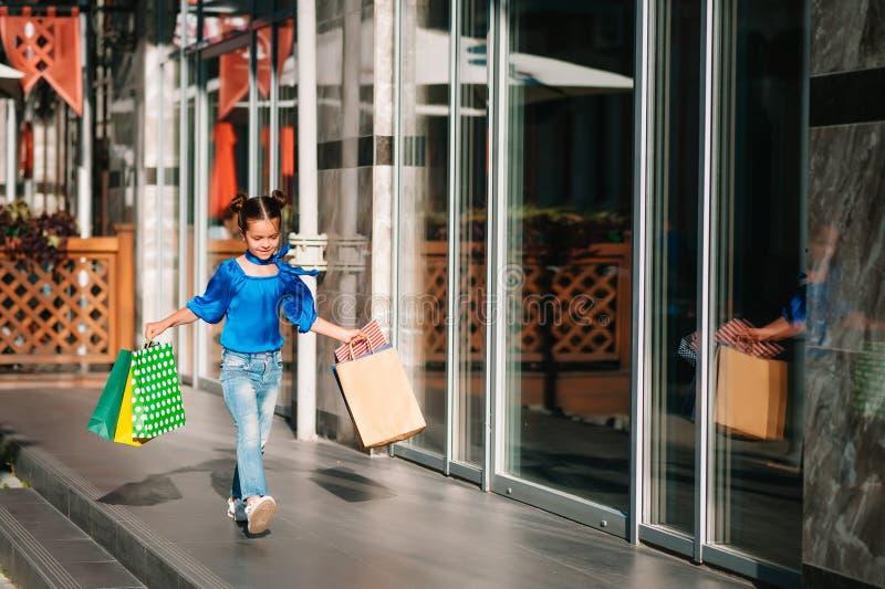 Retrato de una hermosa niña sonriente que lleva saco de compras al aire libre imagenes de archivo