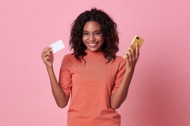 Retrato de una joven africana que muestra tarjetas de crédito y teléfonos celulares aislados sobre fondo rosa imagenes de archivo