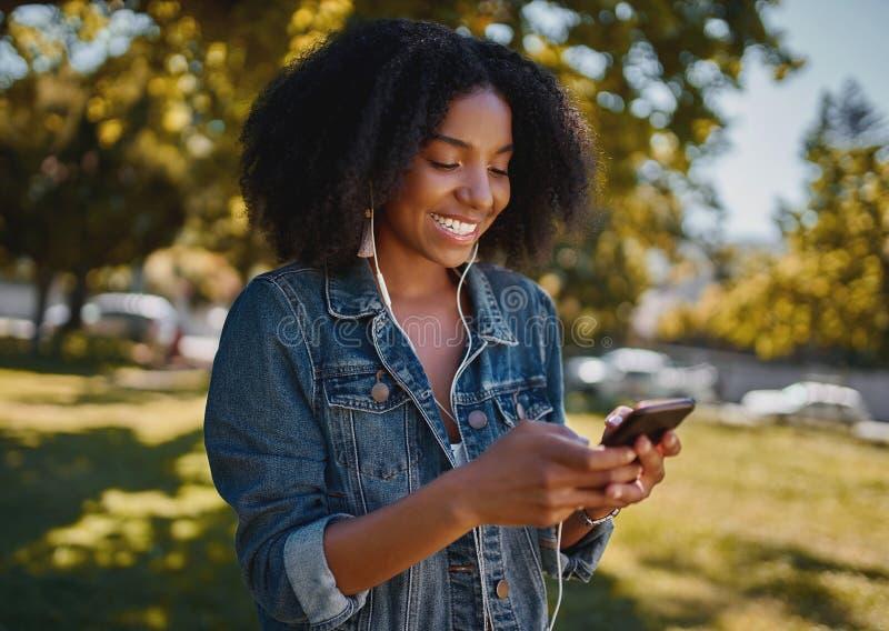 Retrato de una joven afroamericana sonriente y de moda que envía mensajes de texto a través de un teléfono móvil parado en el par fotos de archivo libres de regalías