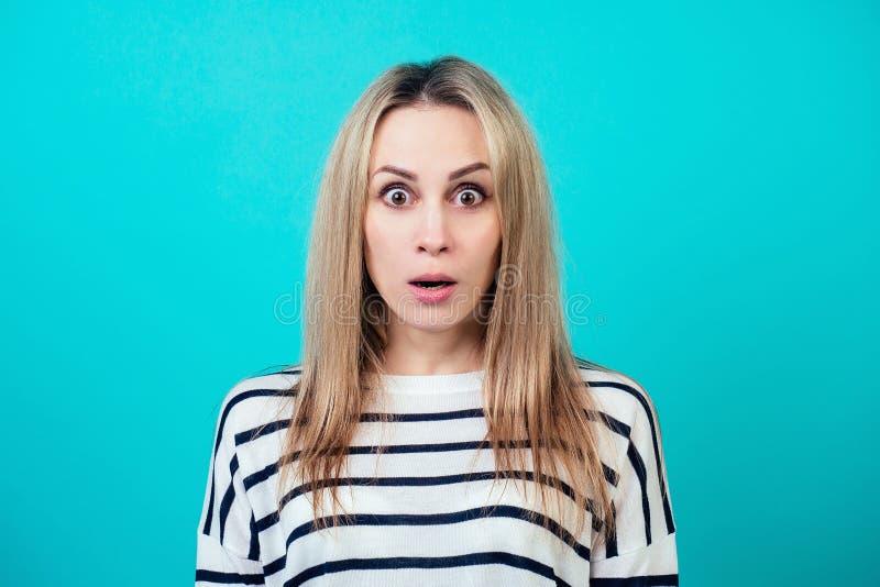 Retrato de una joven atractiva mujer sorprendida con el pelo rubio y boca de maquillaje abierta de sorpresa en el estudio en un es fotografía de archivo libre de regalías