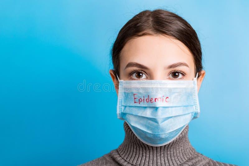 Retrato de una joven con mascarilla médica con palabra epidémica de fondo azul Proteja su salud concepto imagen de archivo libre de regalías