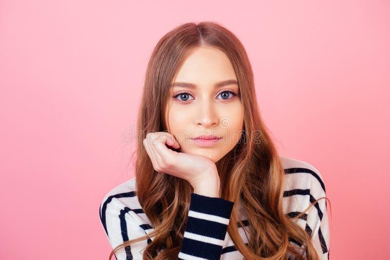 Retrato de una joven y hermosa adolescente aburrida y piensa en un estudio de fondo rosa imágenes de archivo libres de regalías