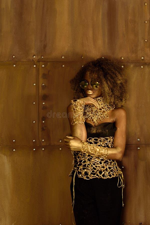 Retrato de una joyería y de gafas de sol del oro de la mujer que lleva africana joven pensativa hermosa que llevan a cabo la mano fotografía de archivo libre de regalías