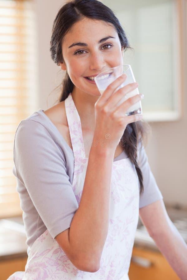 Retrato de una leche de consumo de la mujer magnífica foto de archivo