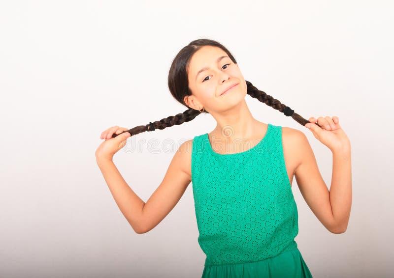 Retrato de una linda chica loca sosteniendo trenzas fotos de archivo libres de regalías