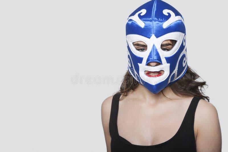 Retrato de una máscara de lucha que lleva de la mujer joven sobre fondo gris fotografía de archivo libre de regalías