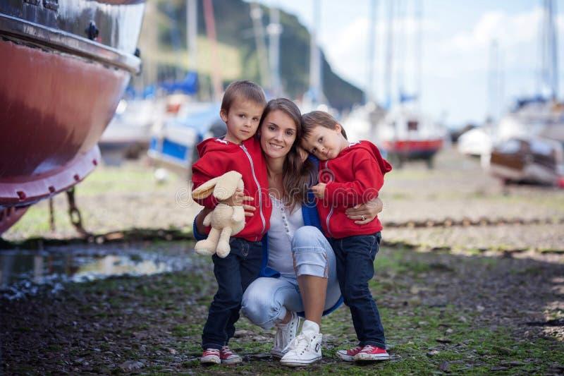 Retrato de una madre con sus dos muchachos, colocándose en un puerto fotografía de archivo libre de regalías
