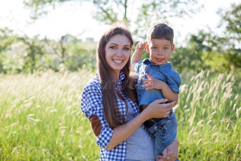 Retrato de una madre con un hijo joven para un paseo en el bosque foto de archivo