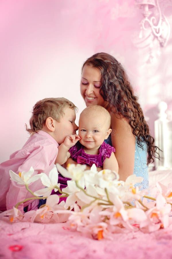 Retrato de una madre feliz y sus niños muchacho y sentada de la muchacha imagen de archivo libre de regalías