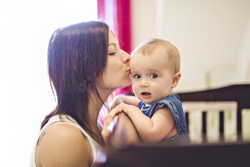 Retrato de una madre hermosa con su bebé de 10 meses foto de archivo