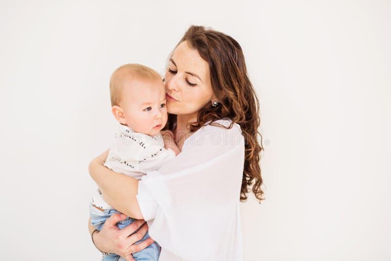 Retrato de una madre joven que besa a su hijo del bebé en casa Copie el espacio foto de archivo