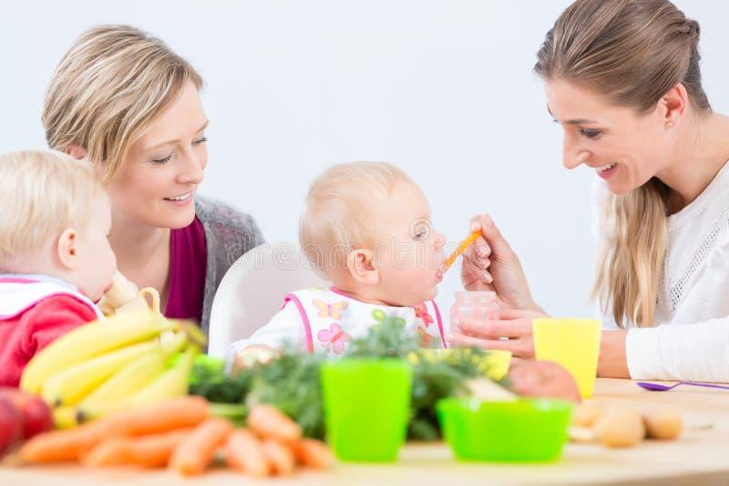Retrato de una madre que aprende de su mejor amigo cómo preparar la comida sana foto de archivo
