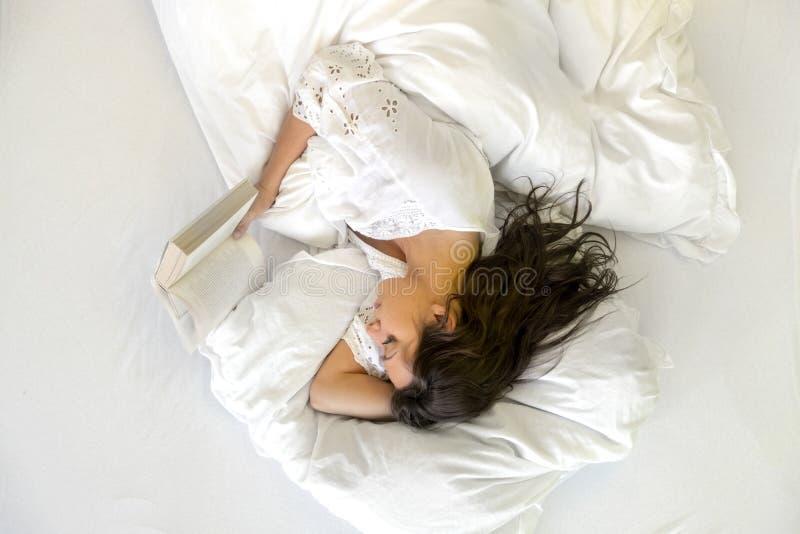 Retrato de una mentira atractiva, contenta, joven, atractiva de la mujer relajada en cama, de gozar y de leer un libro en fresco, foto de archivo