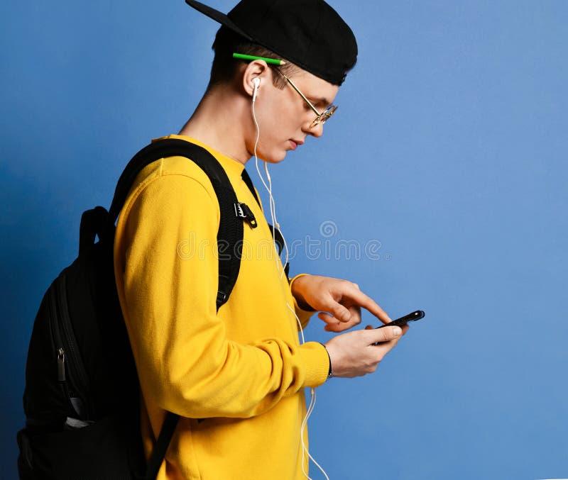 Retrato de una mochila que lleva del estudiante alegre, en casquillo y vidrios y smartphone con sobre fondo p?rpura fotos de archivo