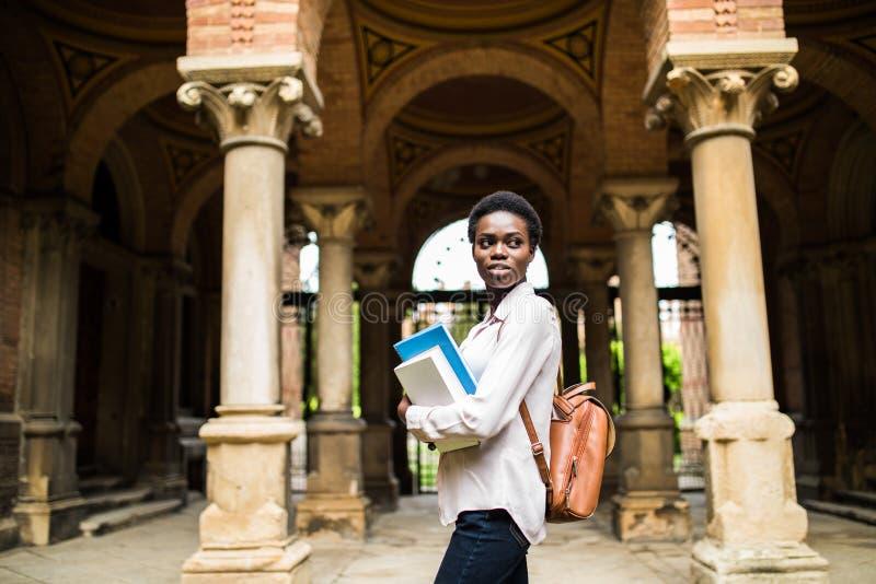 Retrato de una mochila que lleva sonriente alegre de la muchacha africana del estudiante y de los libros el celebrar en el campus imagenes de archivo