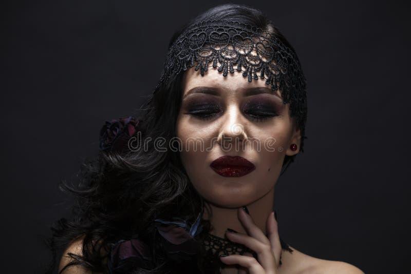 Retrato de una morenita magnífica con un sombrero sobre fondo negro fotos de archivo libres de regalías
