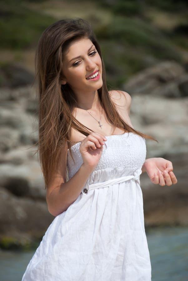 Retrato de una muchacha adolescente con el vestido blanco en la playa fotografía de archivo libre de regalías
