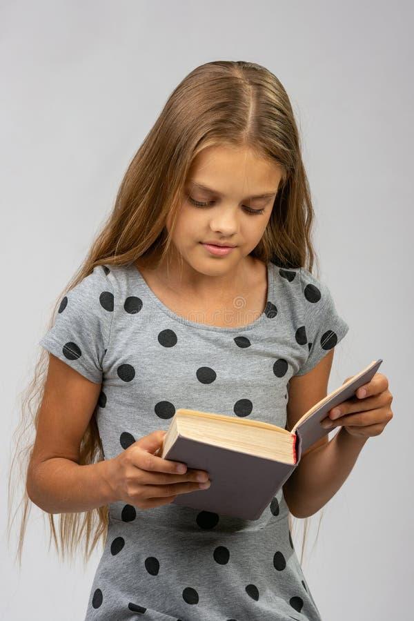 Retrato de una muchacha adolescente que lee un libro imagenes de archivo