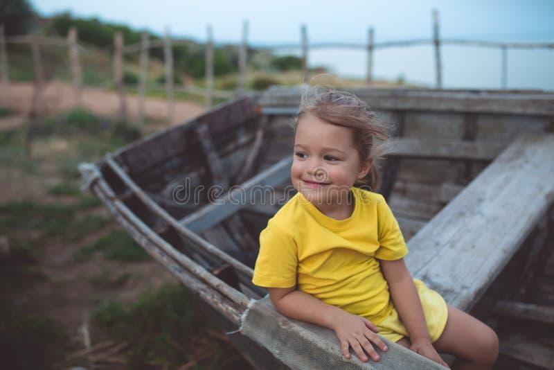 Retrato de una muchacha afortunada, sentándose en un barco viejo en una tarde del verano imágenes de archivo libres de regalías