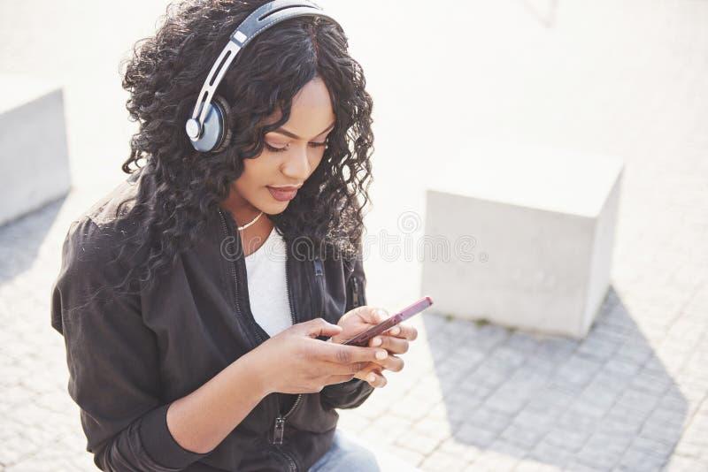 Retrato de una muchacha afroamericana bonita joven hermosa que se sienta en la playa o el lago y que escucha la música en ella fotografía de archivo libre de regalías