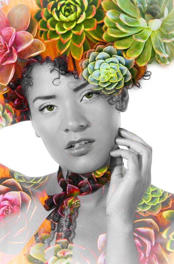Retrato de una muchacha afroamericana hermosa atractiva con un peinado afro, con la exposición doble de plantas exóticas en ella foto de archivo libre de regalías