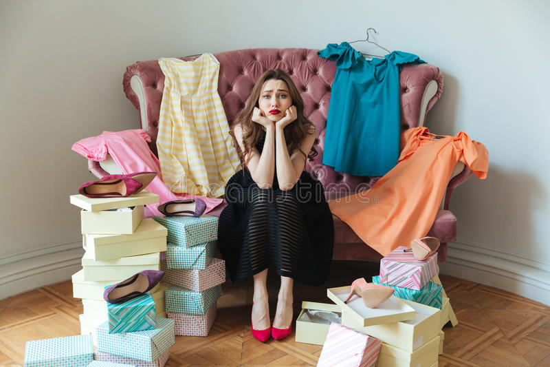 Retrato de una muchacha agotada cansada en el vestido que se sienta en un sofá fotos de archivo libres de regalías
