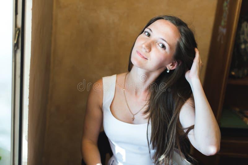 Retrato de una muchacha agradable que fija su pelo imágenes de archivo libres de regalías