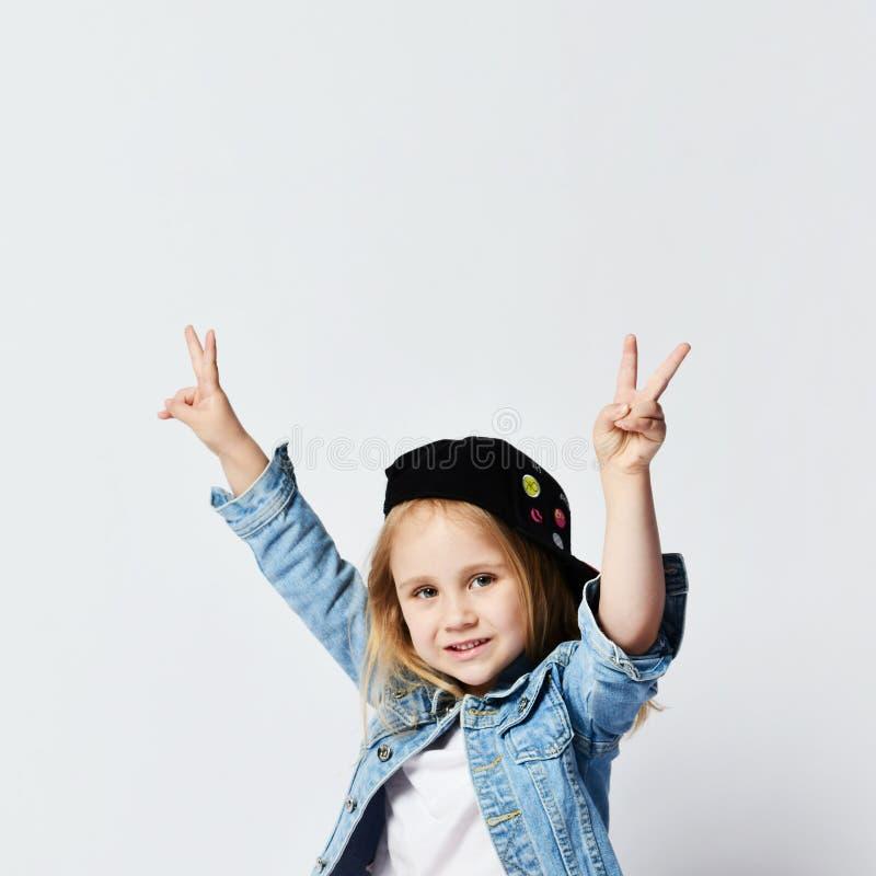 Retrato de una muchacha alegre feliz en el sombrero del verano que muestra gesto de la paz con dos manos foto de archivo