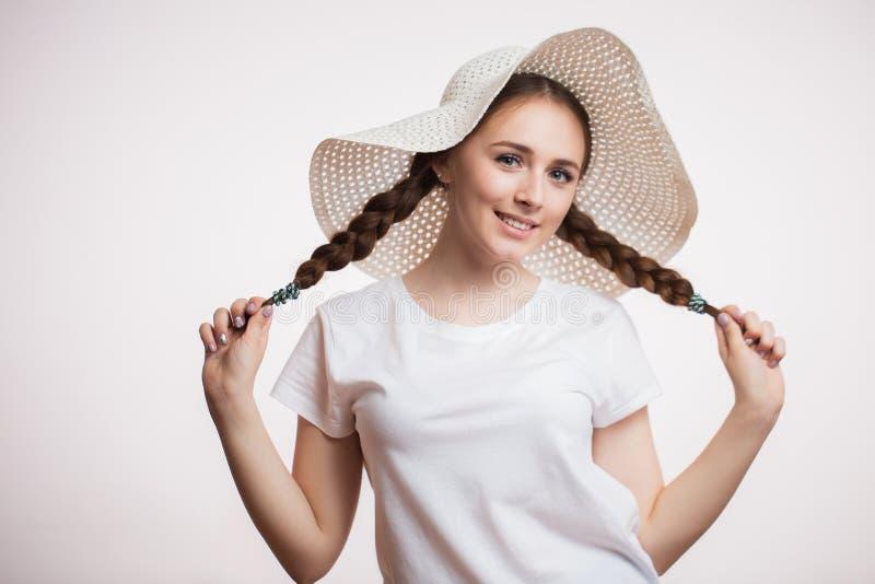 Retrato de una muchacha alegre feliz en sombrero y trenza del verano, de la camisa blanca que lleva y de miradas en la cámara con imagen de archivo