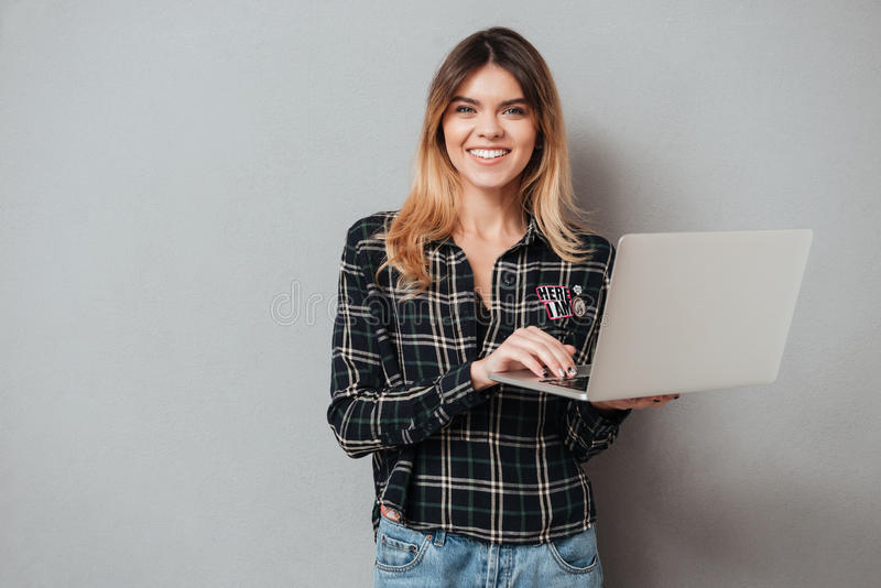 Retrato de una muchacha alegre feliz que usa el ordenador portátil fotografía de archivo