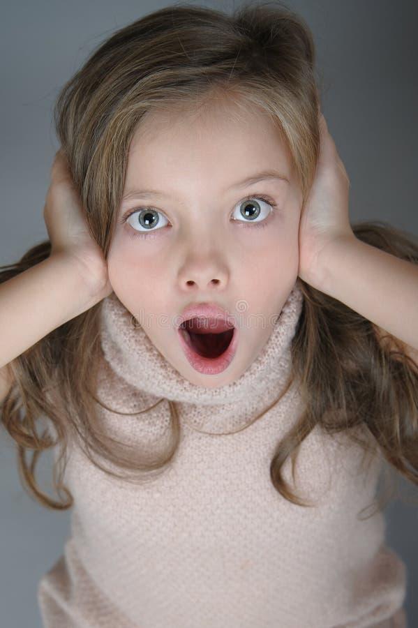 Retrato de una muchacha asustada que se aferra en su cabeza y llora imagen de archivo